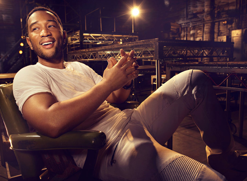 John Legend looks off camera and smiles in a white tshirt