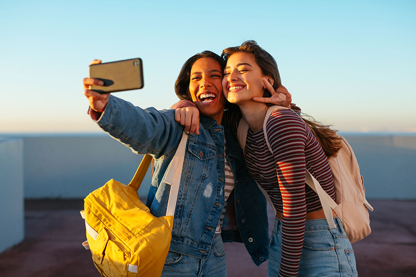 Two VSCO girls pose to take a selfie
