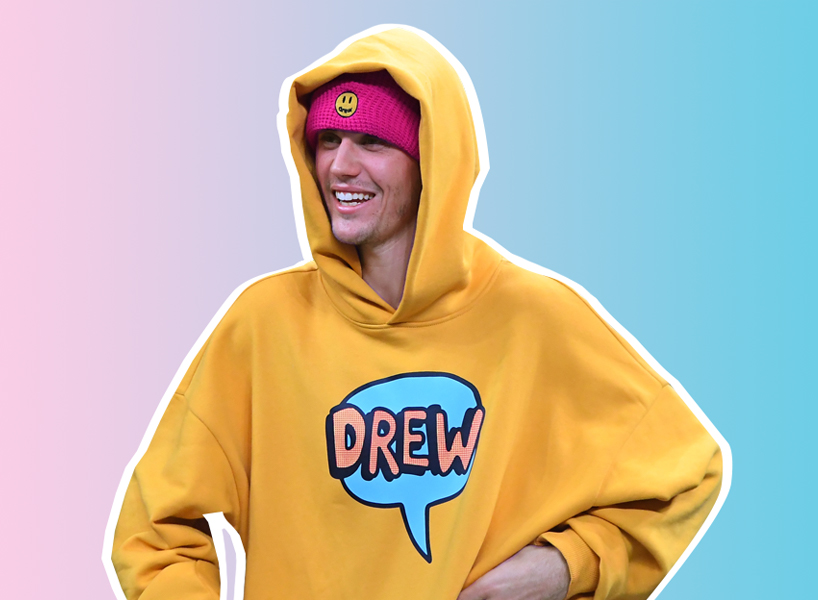 Justin Bieber house messy: Justin Bieber smiles and looks off camera. He is wearing a bright yellow hoodies with a blue text bubble that has the word DREW in pink in it, and a fuschia beanie with a smiley face on the front. His hood is pulled over his head and he stands with his hands on his hips