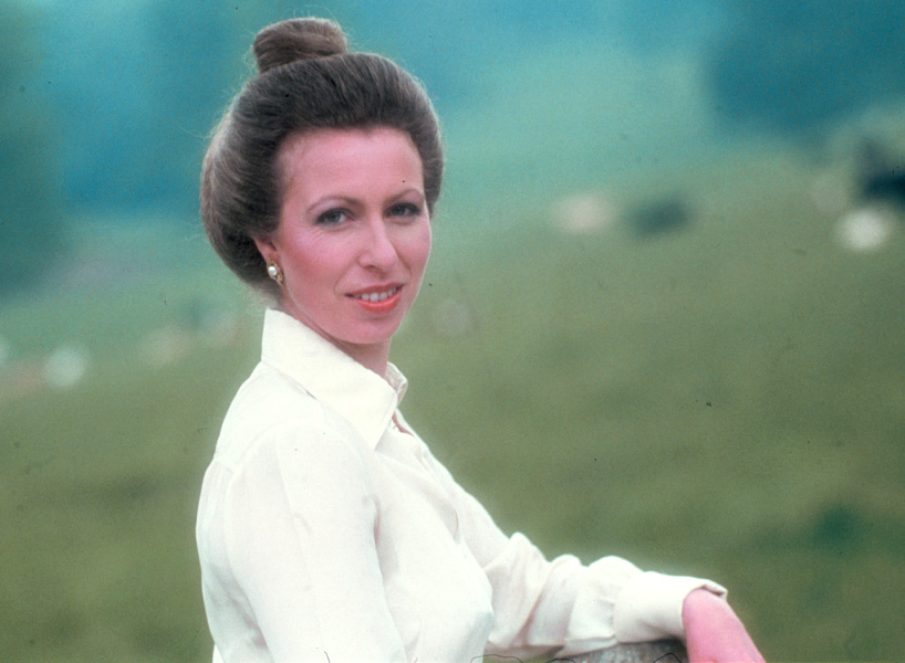Princess Anne looks over her shoulder in an undated photo. She is wearing a white, long-sleeved button up with her hair in a high bun