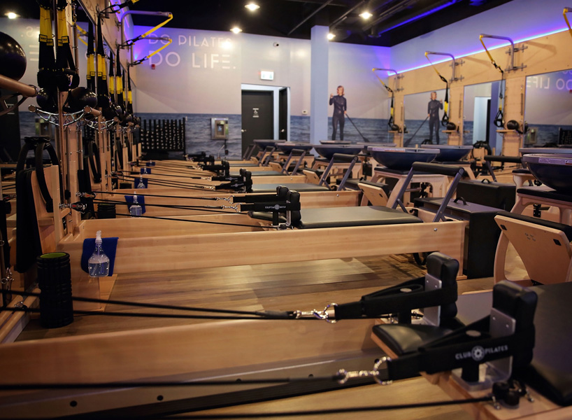club pilates canada: a photo of a club pilates gym in Calgary shows rows of wooden Reformers