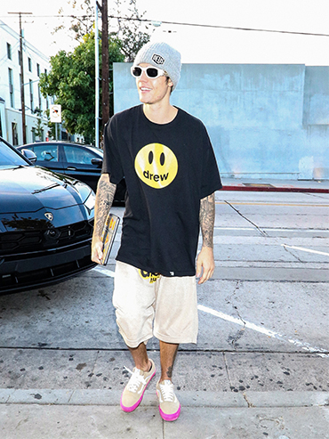 Justin Bieber walks down the street wearing a black tshirt with a yellow smiley face on it, white shorts, a grey toque and black and white sunglasses