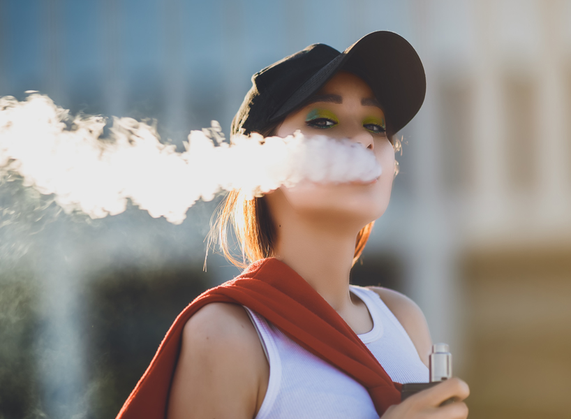A young woman exhales smoke holding a vape pen, looking at the camera.