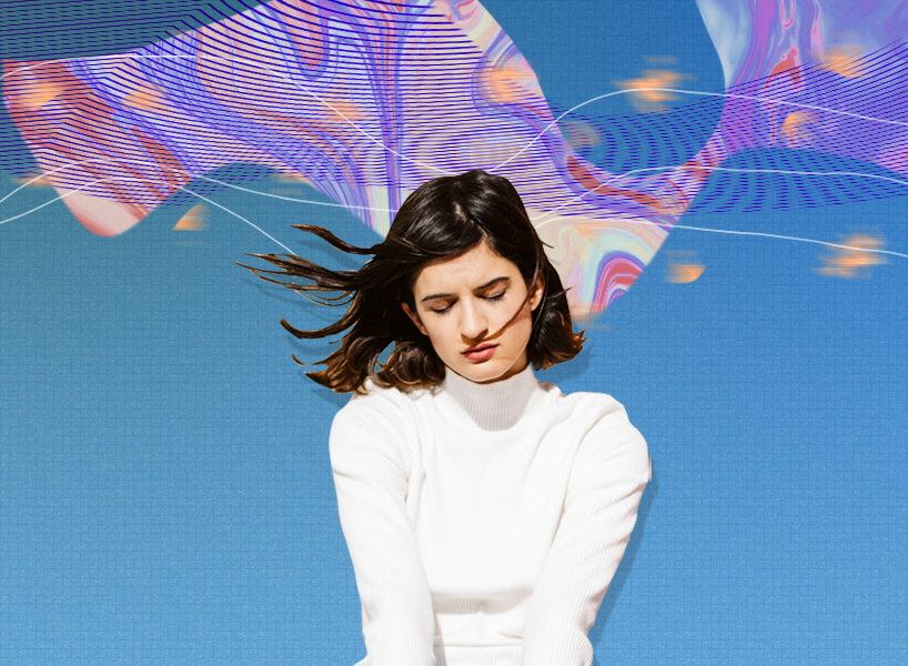 a woman in a white turtleneck top against a multi-coloured background