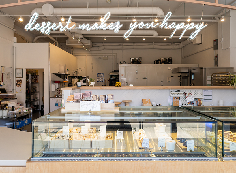 Best bakery in Toronto: Roselle West's counter with a neon sign reading 'dessert makes you happy' above it.