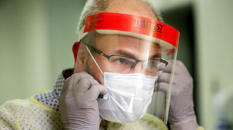 Coronavirus in Canada: Someone demonstrates how to put on a face mask and protective clothing during a tour of a COVID-19 evaluation clinic in Montreal.