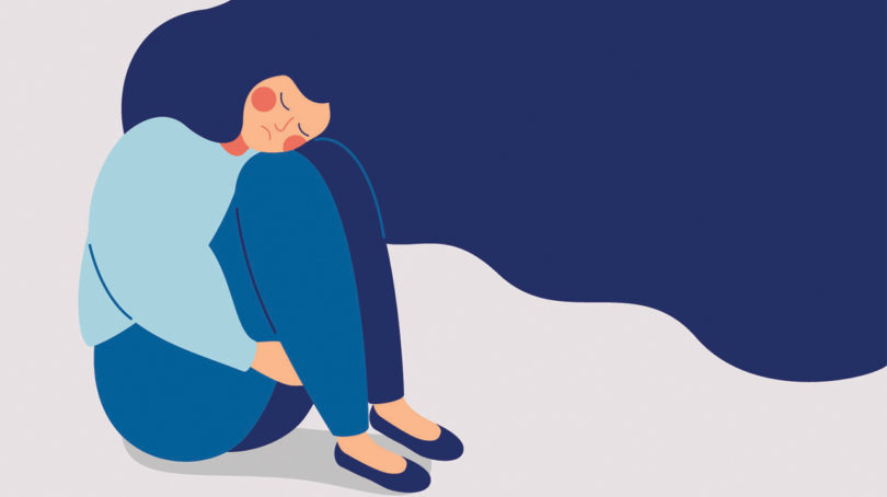 A blue illustration of someone holding their knees to their chest looking sad, with long hair flowing into the sky. The background is greyish-pink to illustrate this story on managing anxiety during covid 19