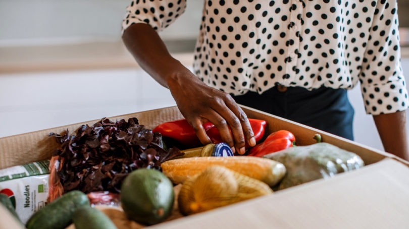 Someone reaches into a box of produce in a photo to illustrate a story on home delivery grocery services in Canada