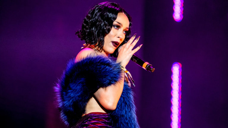 doja cat cancelled racism: Doja Cat performs on-stage in a purple, furry stole