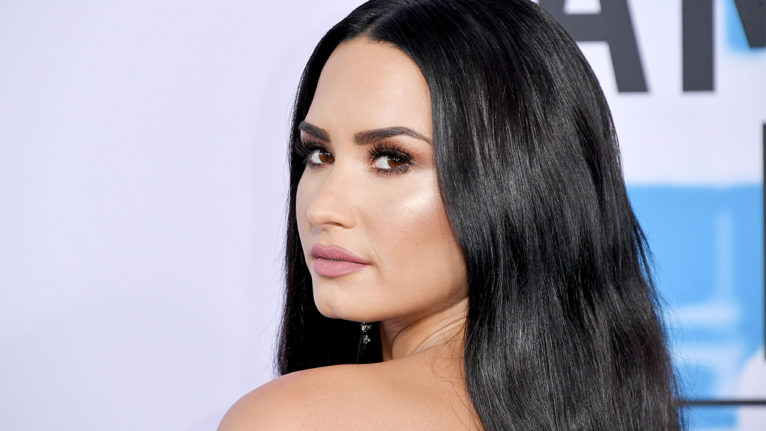 demi lovato engaged max ehrich: Demi Lovato looks over her shoulder and poses. Her hair is down and in waves