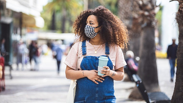 is a pandemic baby boom actually coming: A pregnant woman in overalls places her hand on her bump. She's holding a coffee in one hand and is wearing a mask