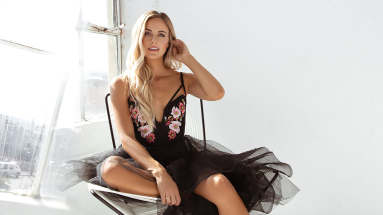 bachelor kendall long book: Kendall Long poses in a black and floral dress. She is sitting on a chair looking directly at the camera