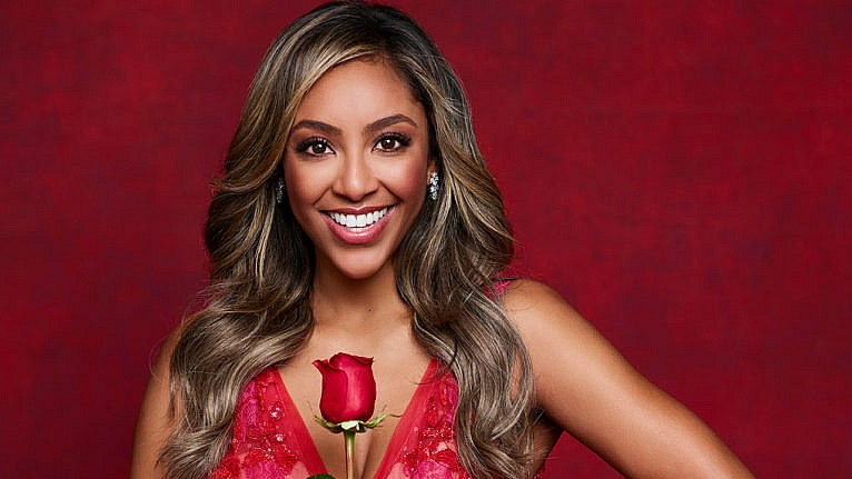 the bachelorette tayshia adams contestants: Tayshia Adams smiles at the camera and holds a rose