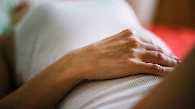 what is health care gaslighting? A picture of a woman lying on her back with her hand on her stomache