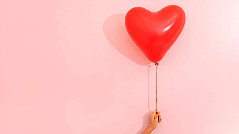how to survive cuffing season: A stock photo of a red heart balloon