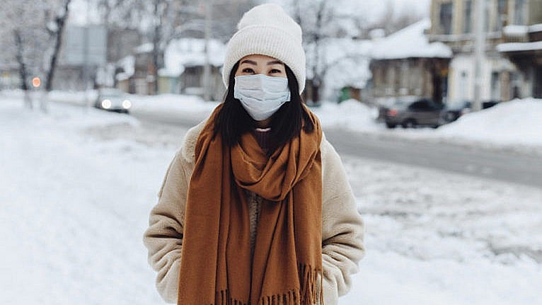 Young woman with black hair is standing outside in the snow wearing a medical face mask, brown scarf, beige coat and white winter hat