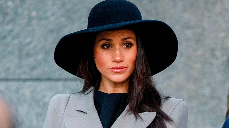 Meghan Markle wearing a black wide-brimmed hat and a grey blazer