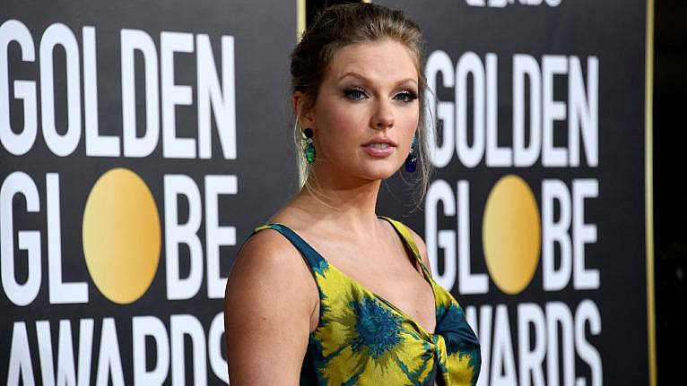 Taylor Swift, from the shoulders up, posing on the Golden Globes 2021 red carpet wearing a colourful gown
